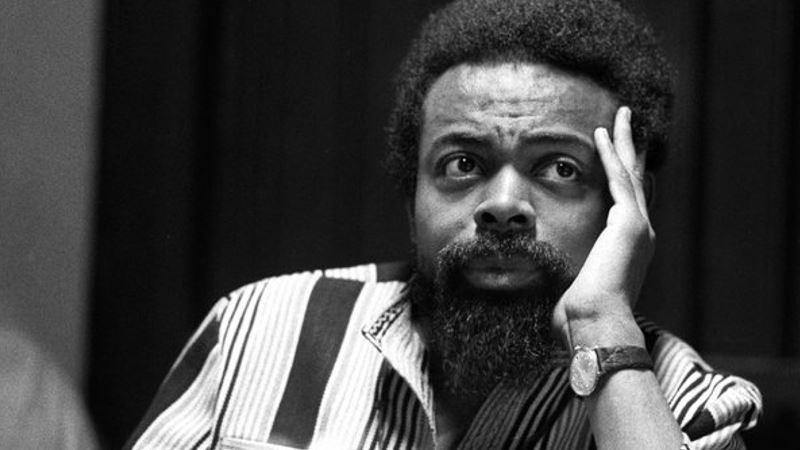 Black and white i,mage of Amiri Baraka facing the camera while looking up