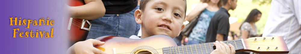 A young boy holding a guitar at the Hispanic Festival