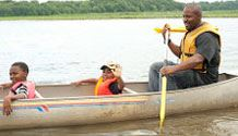 a father with two children wearing life jackets while canoeing in water.