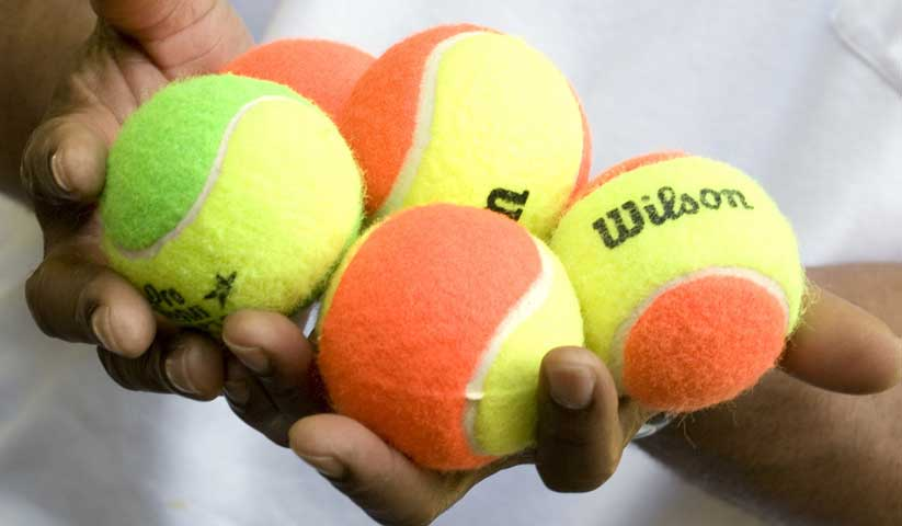 Closeup of five colorful tennis balls being held in a person's hands.